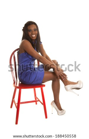 An African American woman sitting on a chair in her blue dress.