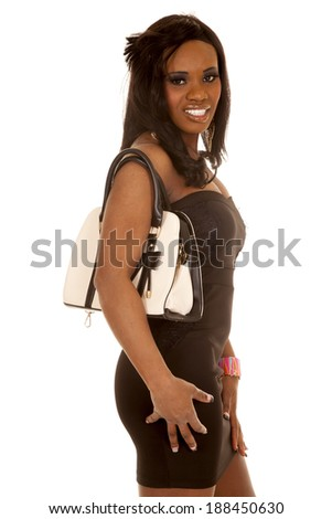 An African American woman standing carrying a purse on her shoulder. - stock photo