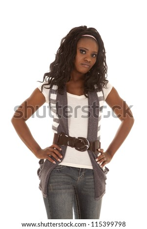 An African American woman standing in her cute clothes with her hands on her hips and a serious expression on her face. - stock photo