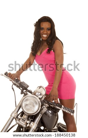 an African American woman standing on her motorcycle.