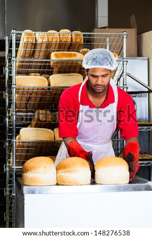an african baker wearing red heat protection gloves placing white round bread loaves on to a counter top to cool - stock photo