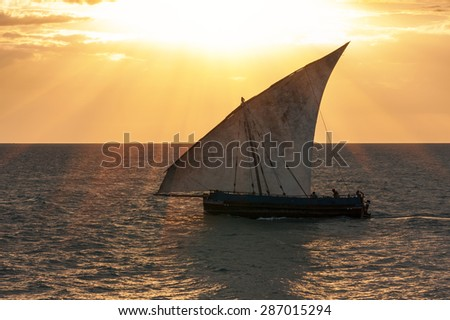 an african dhow sailboat sailing with full sail to the wind the warm golden glow of the suns rays over the sea and sky - stock photo