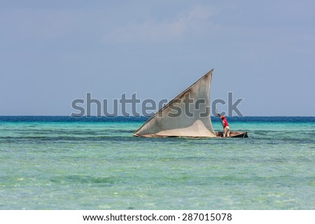an African fisherman heading out over a reef sailing in his small dhow fishing boat sail full to the wind - stock photo