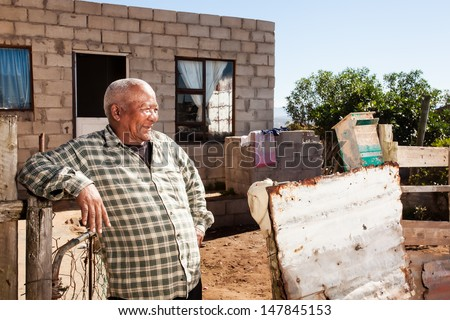 an african man leaning confidently against his fence smiling in front of his brick home in the township