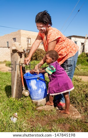 an african mother happily washing her daughters hand under running water in the township - stock photo