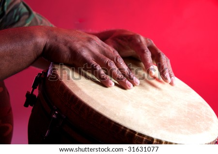An African or Latin Djembe being played against a red background in the horizontal format.