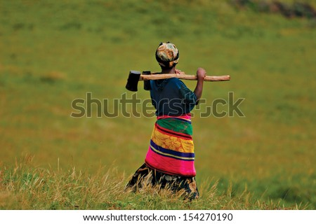 An African woman carries an axe in a field. - stock photo