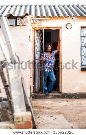 an african woman dressed in casual print posing at her front door with pride towards her brick home with a corrugated roof - stock photo
