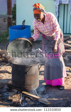 An african woman is making food the traditional way. - stock photo