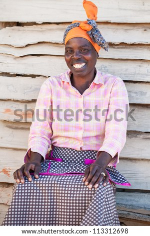 An African woman outside of her home - stock photo
