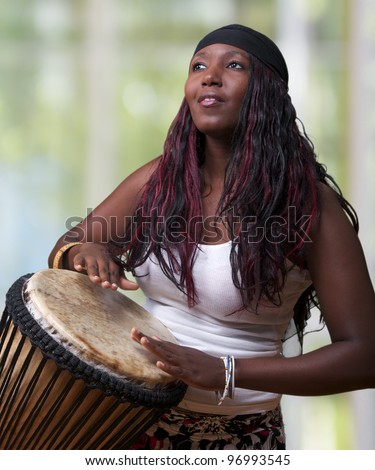 An African woman plays the djembe drum - stock photo