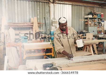 An african worker putting varnish on a plank