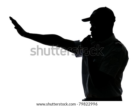 An afro American traffic cop making stop gesture while blowing whistle in studio on white isolated background - stock photo