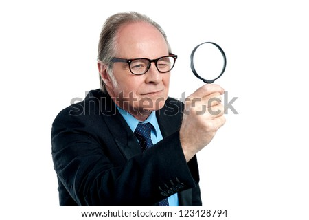 An aged detective exploring through a magnifying glass isolated on white background.