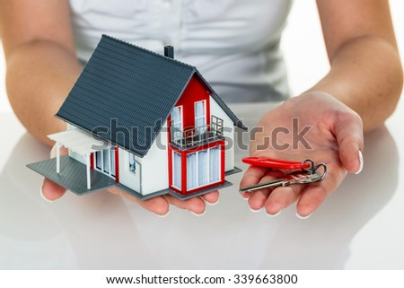 an agent for property with a house and a key. successful leasing and property sales by real estate brokers.