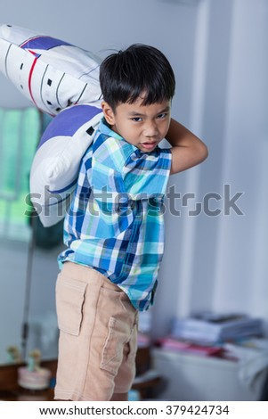 An aggressive asian child. Boy looking furious. Kid will throw pillow inside bedroom. Negative human face expressions, emotions .problem families concept. - stock photo