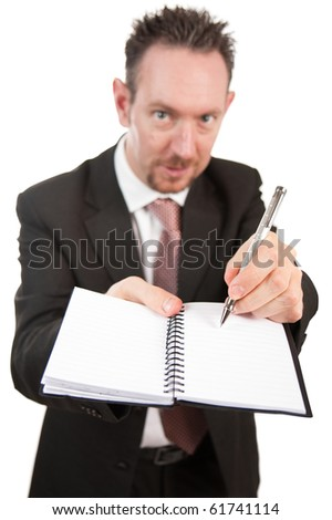 An aggressive looking businessman holds an open notebook and points at something on the book with his pen.  The pad is blank.  Differential focus on the pen and pad. - stock photo