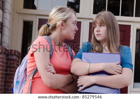 An aggressive teen girl intimidates another girl in front of their school, probably over a boy. - stock photo
