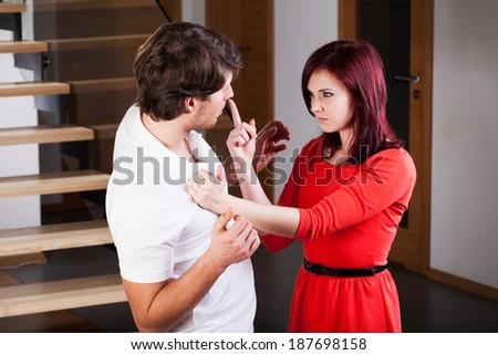 An agressive woman threatening her boyfriend - stock photo
