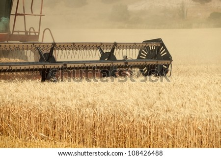 An agricultural combine cutting and harvesting wheat in the fertile farm fields of Idaho. - stock photo