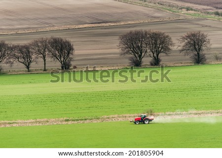 An agricultural tractor during a fertilizer treatment in springtime. - stock photo
