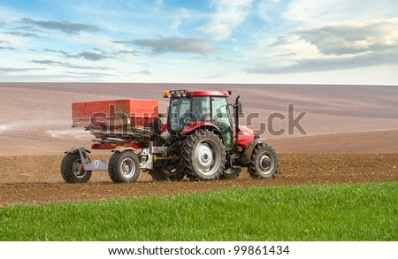 an agricultural tractor starts a chemical treatment run across new growing crops, with copy space below.