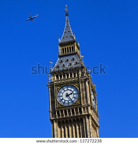 An aircraft flying high over the Houses of Parliament in London. - stock photo