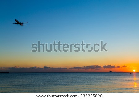 An airplane approaching the runway for landing during the sunset - stock photo