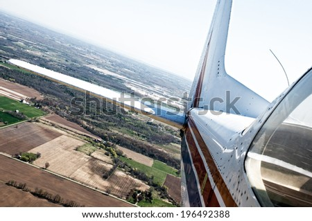 An airplane flying above fields and trees on a sunny day.