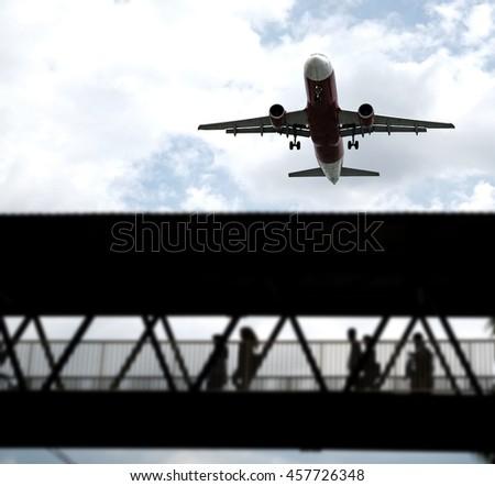 An airplane flying over an airport pedestrian walkway bridge.  - stock photo