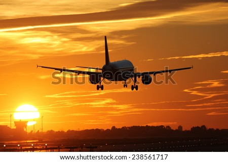 An airplane landing at an airport during sunset on vacation during a journey