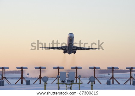 An airplane taking off on a cold winters evening - stock photo