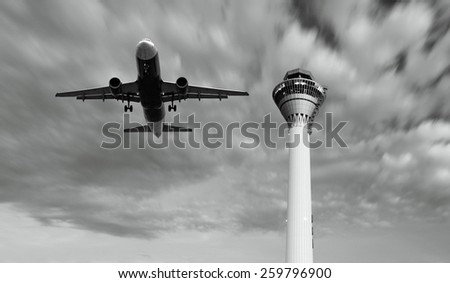 An airplane taking off over an airport control tower.  - stock photo