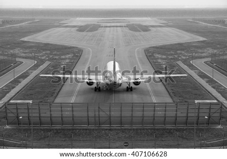 An airplane taxiing on an airport runway, processed in monochrome.