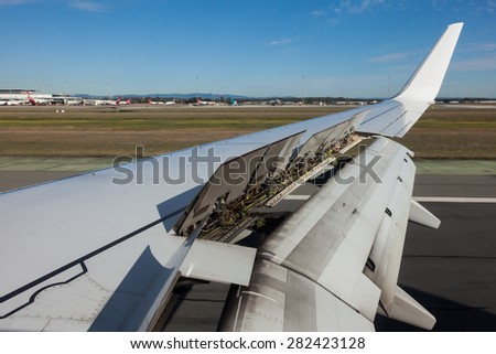 An airplane window view of wing and flaps after landing. - stock photo