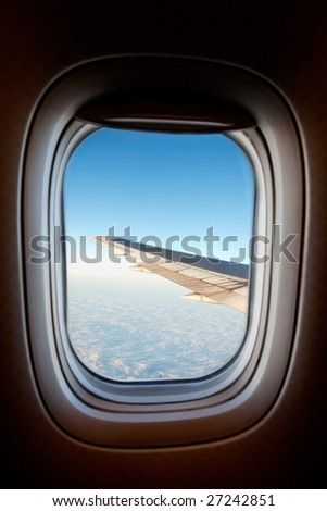 An airplane window with wing and cloudscape - stock photo