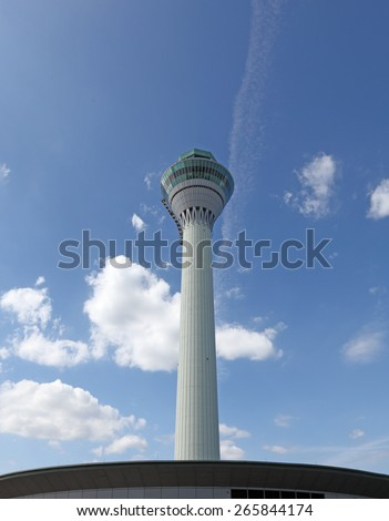 An airport air traffic control tower against a clear blue sky.  - stock photo