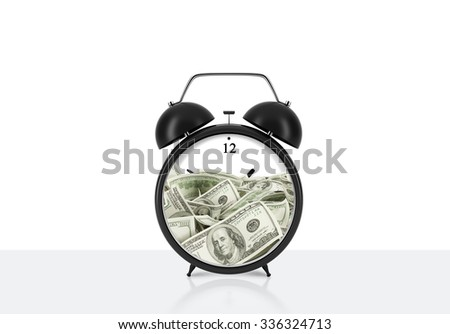 An alarm clock with dollar bills inside is on the table. The concept of 'time is money' and a time management. White background.
