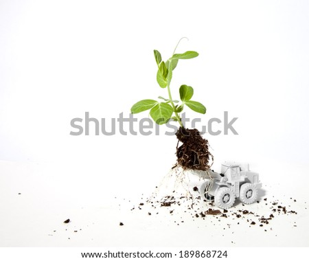 An all white miniature construction vehicle lifts a small sprout with roots and dirt. - stock photo
