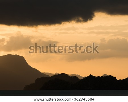 An amazing sunset view in the tropics. The sky is golden orange and the mountains in the distance look magical. Dark clouds frame the picture perfectly. Tanjung Rhu Beach, Langkawi, Malaysia.