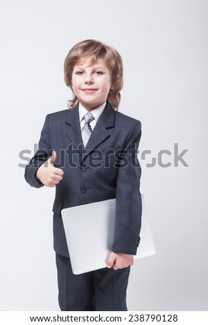 an ambitious young man in shirt and tie with a laptop and looking at the camera - stock photo