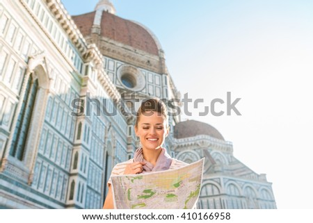 An amble around awe-inspiring Duomo in Florence, Italy. Happy woman tourist looking at the map while standing in the front of Duomo - stock photo