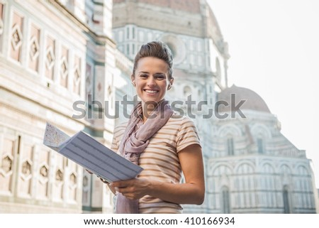 An amble around awe-inspiring Duomo in Florence, Italy. Portrait of happy woman tourist with a map listening to the audio guide - stock photo