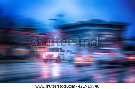 an ambulance racing through the rain on a stormy night with motion blur (NO SHARP FOCUS DUE TO RAIN and slow shutter speed) with reflections in the road  - stock photo