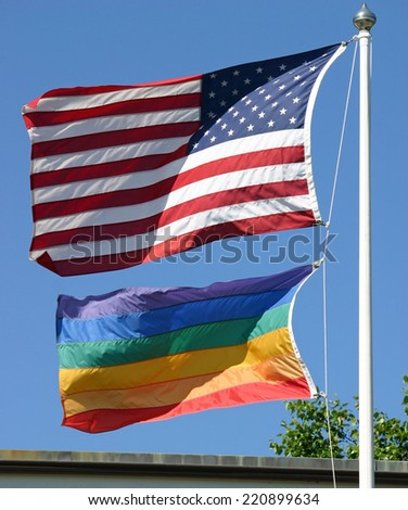 An American and a gay pride flag waving in the wind - stock photo