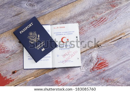 An American and Turkish passport lying on an old wooden table with the Turkish passport opened to reveal a cancelled hand stamp conceptual of immigration and changing citizenship - stock photo