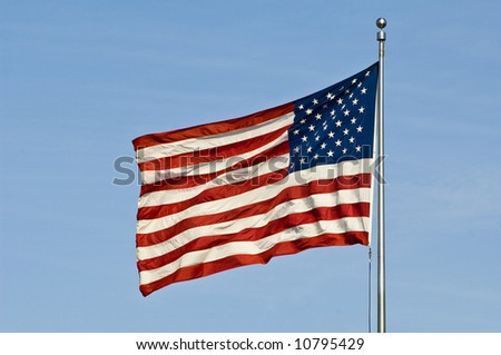 an American flag waves in the breeze against blue