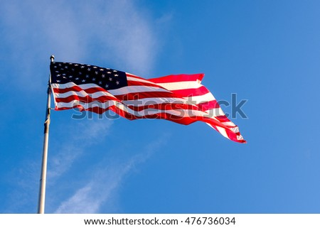 an American flag waves in the wind with blue sky in the background
