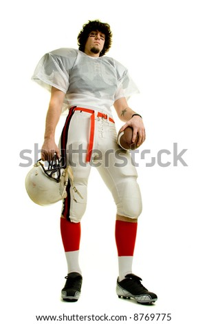 An American football player. Standing with helmet and ball.