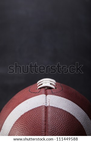 An American football with a chalkboard in the background for copy-space. - stock photo